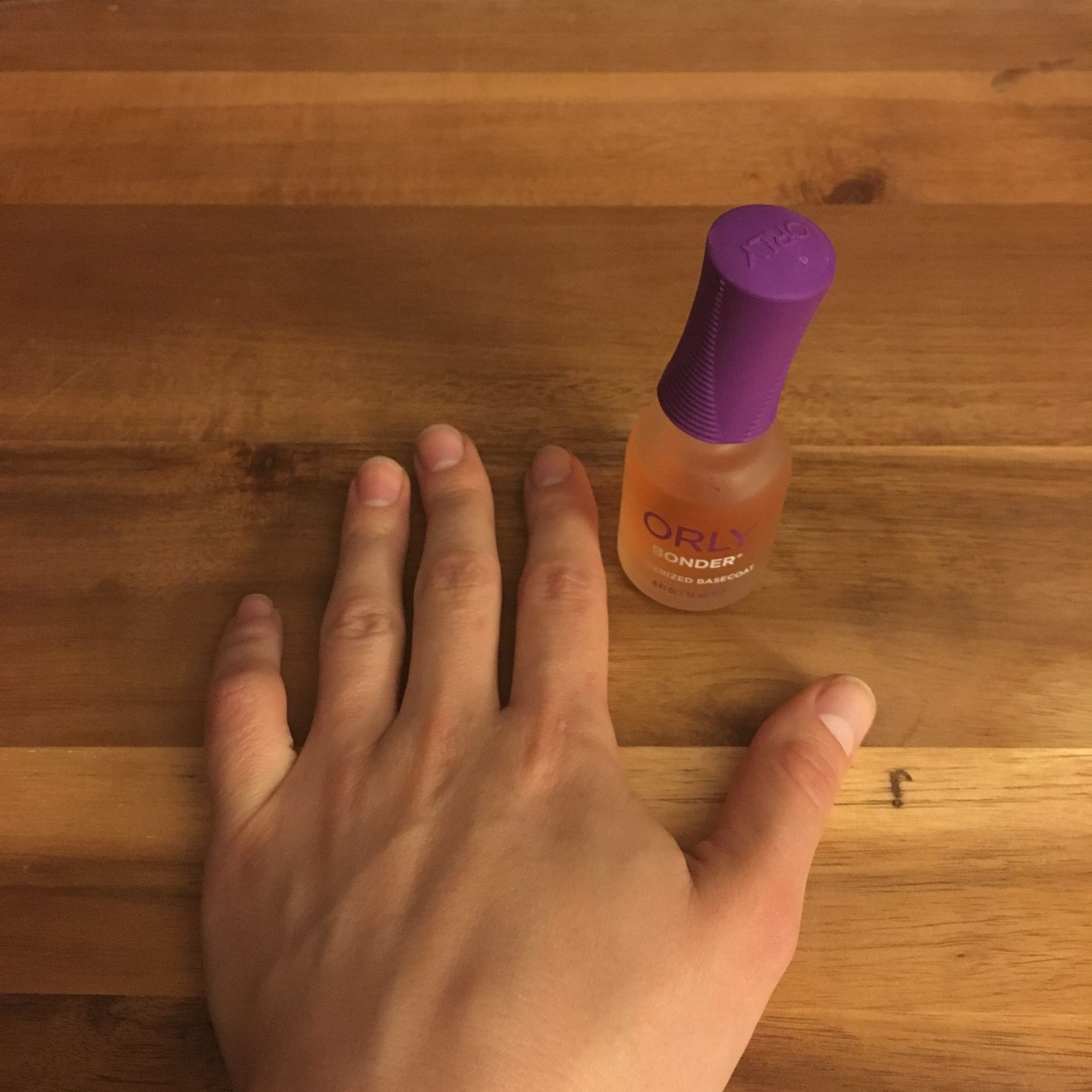 Glass of Glam Nails | Glass of Glam Nails | At Home Manicure Tips by popular Chicago beauty blog, Glass of Glam: image of a woman's hand next to a bottle of Amazon Orly Base Nail Coat.