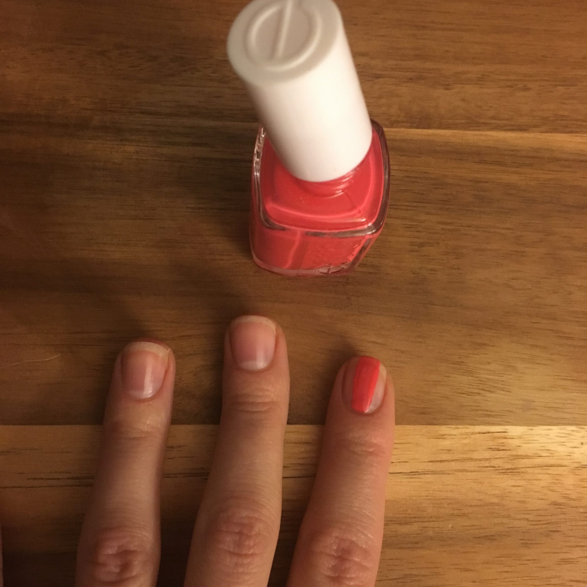 Glass of Glam Nails | At Home Manicure Tips by popular Chicago beauty blog, Glass of Glam: image of a woman's hand next to a bottle of Amazon essie Nail Polish, Glossy Shine Finish, Peach Daiquiri.