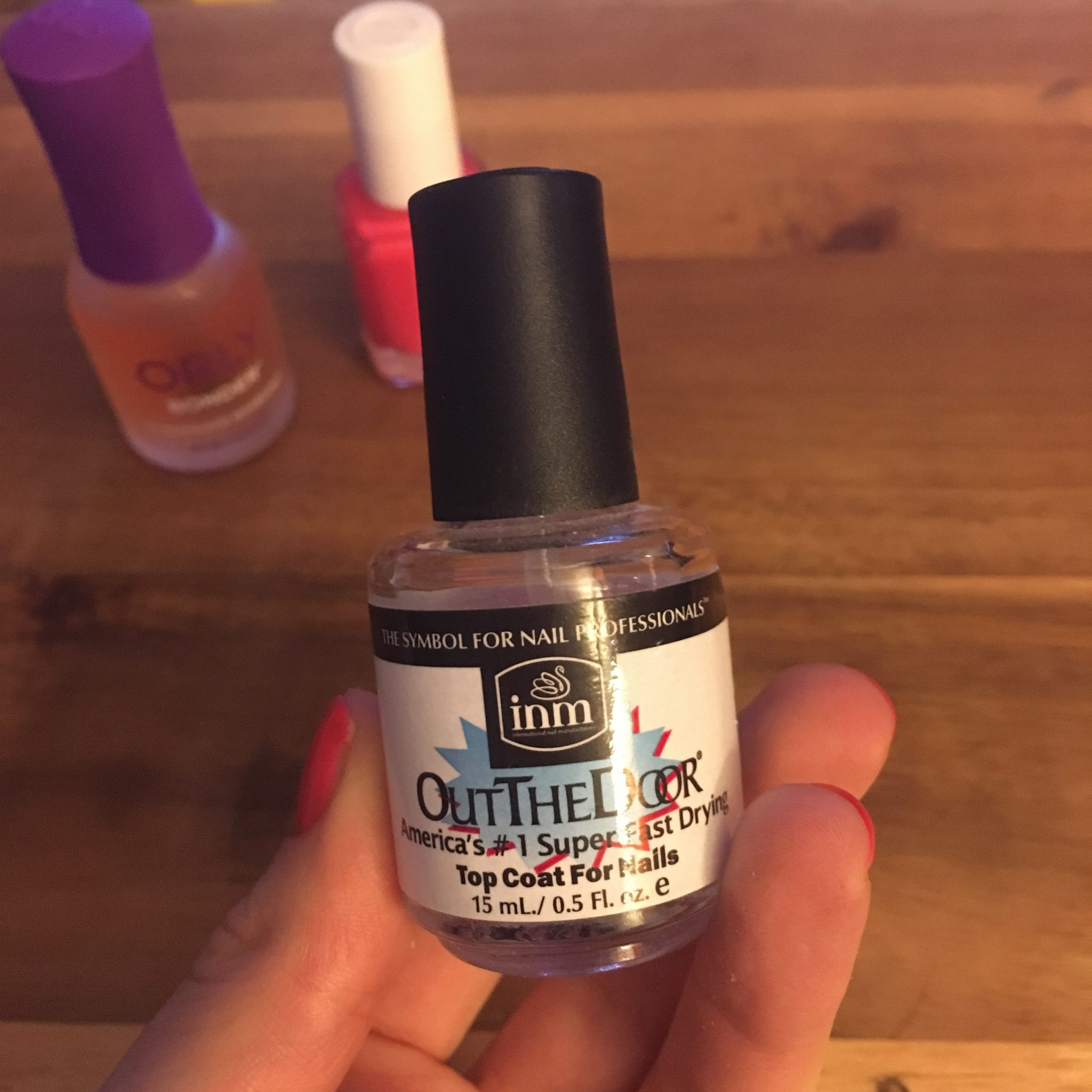 Glass of Glam Nails   At Home Manicure Tips by popular Chicago beauty blog, Glass of Glam: image of a woman holding a bottle of Amazon Out The Door topcoat.
