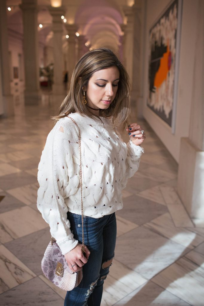 Lifestyle Blogger Roxanne Birnbaum of Glass of Glam wearing a Free People sweater, Lulus heels, Express denim, Shein saddle bag, a choker necklace, and Sophie Blake New York Earrings