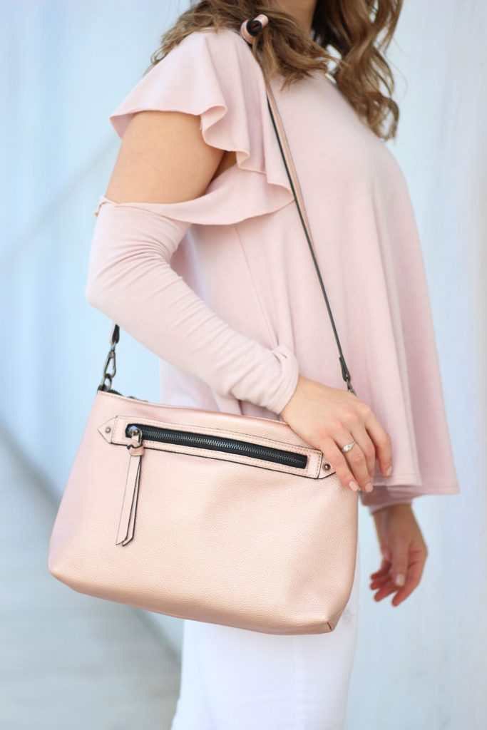 Lifestyle blogger Roxanne Birnbaum of Glass of Glam wearing a Red Dress Boutique pink ruffle top, Old Naby distressed denim, and a JustFab rose gold bag