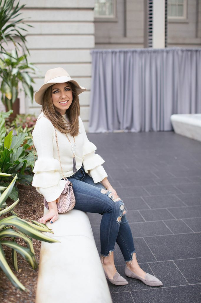Lifestyle Blogger Roxanne Birnbaum of Glass of Glam wearing a Shein ruffle sweater, saddle bag, M.Gemi flats, and Express distressed denim