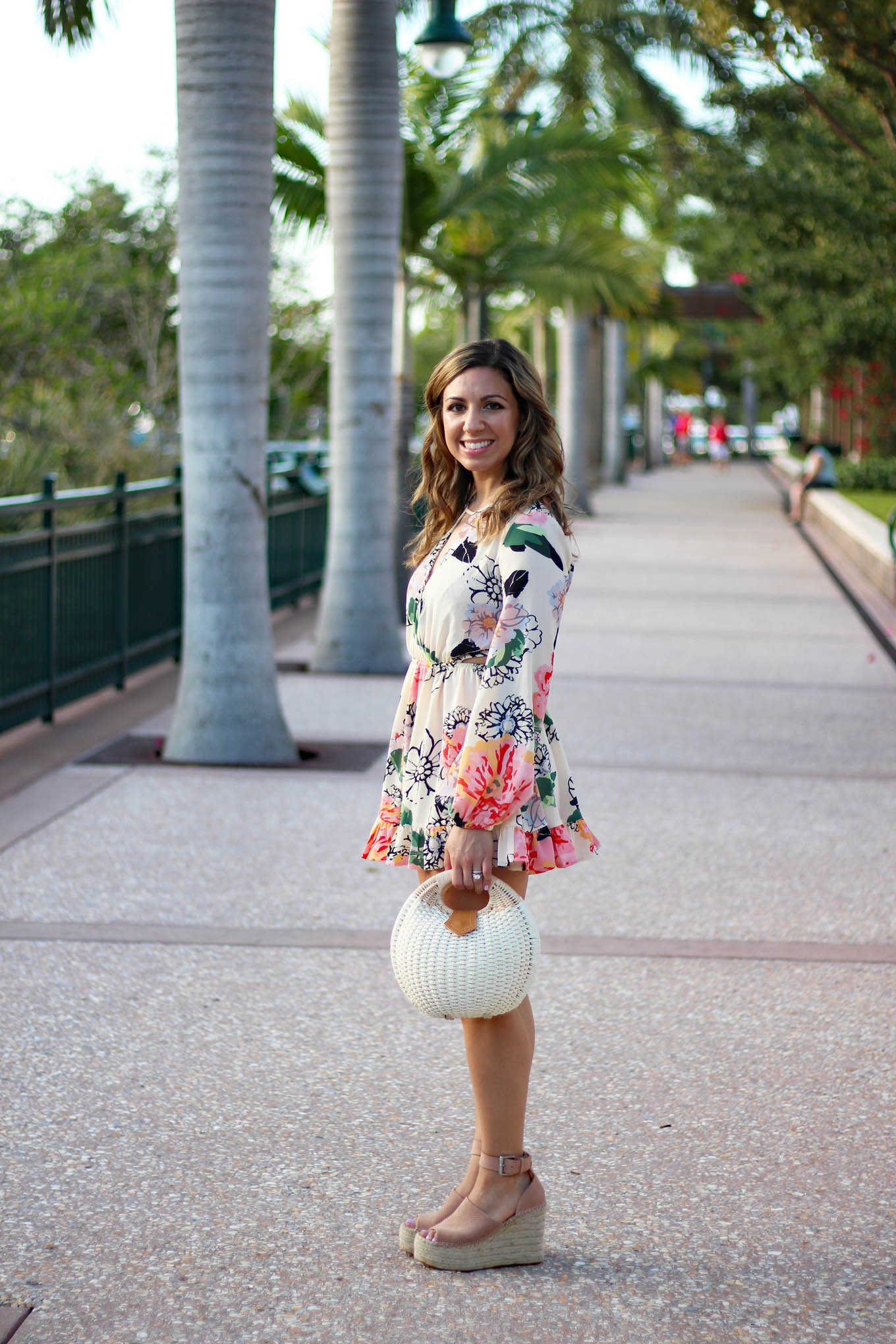 Lifestyle Blogger Roxanne Birnbaum of Glass of Glam in a Floral Ruffle Zaful romper, Marc Fisher Wedge Espadrilles, and a Zaful Basket Bag