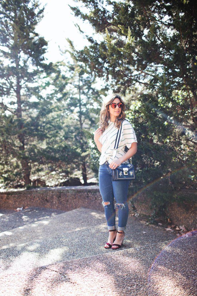 Style Blogger Roxanne Birnbaum of Glass of Glam wearing a SugarLips striped top, AG denim, Amazon Fashion coat, a Zaful bag, and Vye Eyewear Sunglasses
