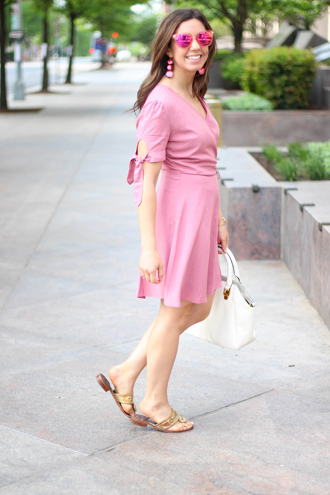 Lifestyle Blogger Roxanne of Glass of Glam in a Pink wrap dress and Baublebar pom pom earrings
