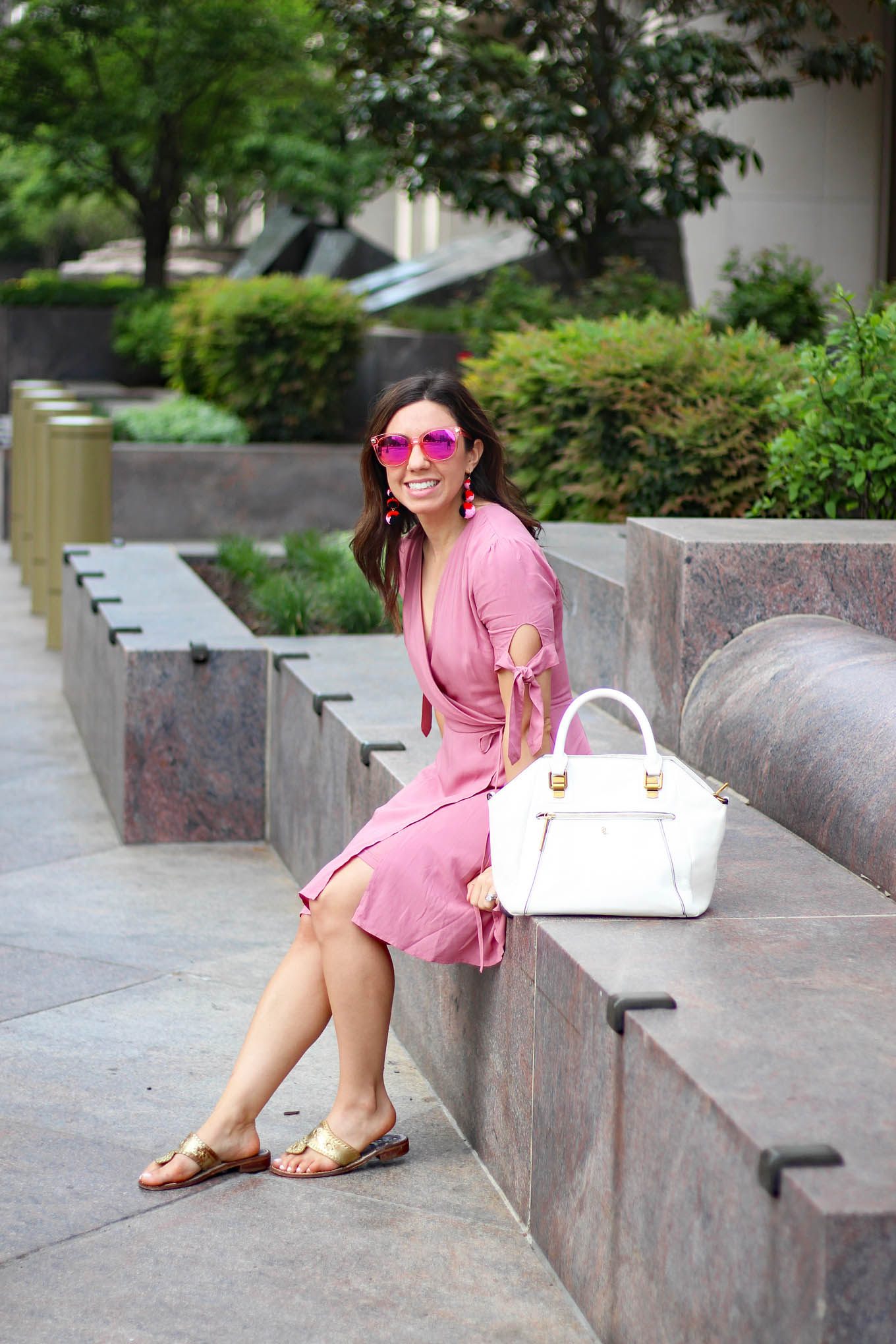 Lifestyle Blogger Roxanne of Glass of Glam in a Pink wrap dress and Baublebar pom pom earrings and an Elliott Lucca white satchel