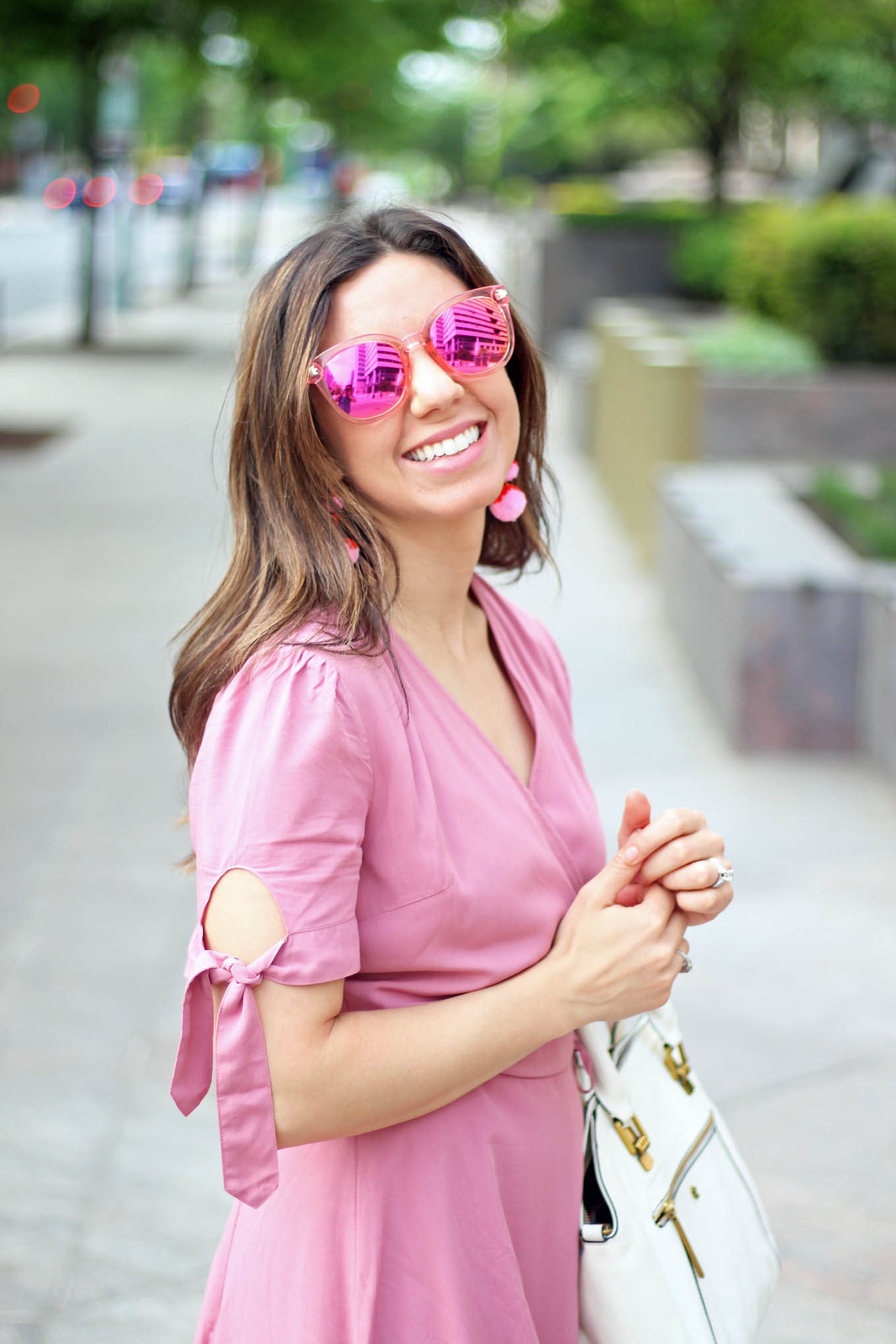 Lifestyle Blogger Roxanne of Glass of Glam in a Pink wrap dress and Baublebar pom pom earrings and Zaful pink sunglasses