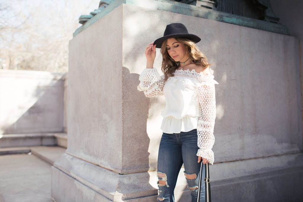 Lifestyle Blogger Roxanne of Glass of Glam wearing a SheIn lace off the shoulder top, Express denim, Justfab Shoes, Zaful bag, and a feathered fedora