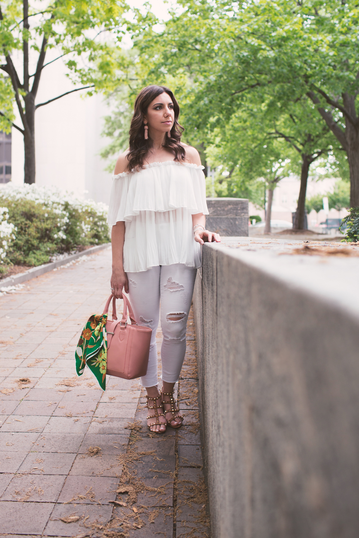 Lifestyle blogger Roxanne of Glass of Glam wearing a Goodnight Macaroon off the shoulder top, Old Navy denim, Lisi Lerch tassel earrings, and a silk scarf