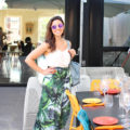 Lifestyle blogger Roxanne of Glass of Glam wearing a palm print skirt, Justfab Tote, and Warby Parker Sunglasses