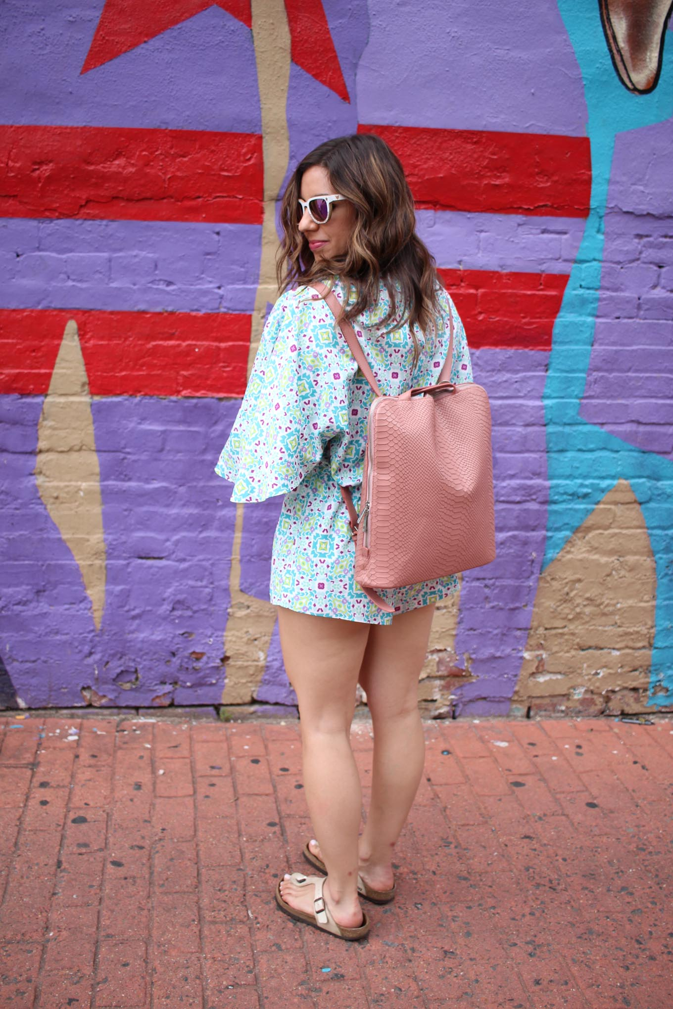 Lifestyle blogger Roxanne of Glass of Glam wearing a Cuddy Studios Romper, Winkwood Sunglasses, and a Mel Boteri bag