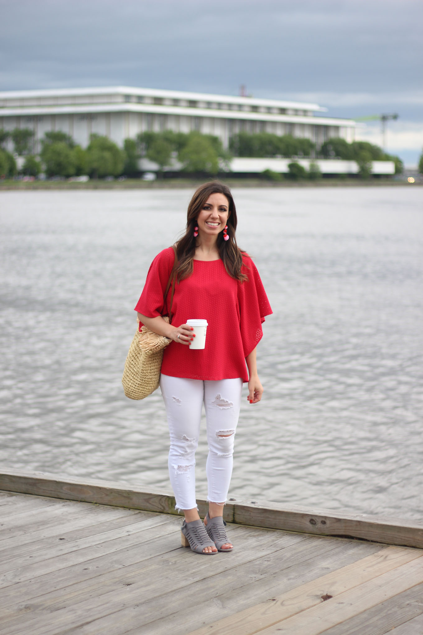 Lifestyle blogger Roxanne of Glass of Glam wearing a red Cuddy Studios top, Baublebar earrings, a straw tote, and Old Navy Denim