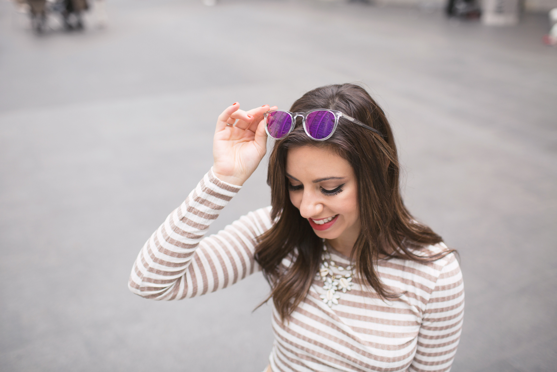 Lifestyle blogger Roxanne of Glass of Glam wearing a striped crop top, Old Navy denim, and warby parker sunglasses