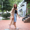 Lifestyle blogger Roxanne of Glass of Glam wearing a Justfab duster cardigan, distressed denim skirt, and pink Gucci dupes