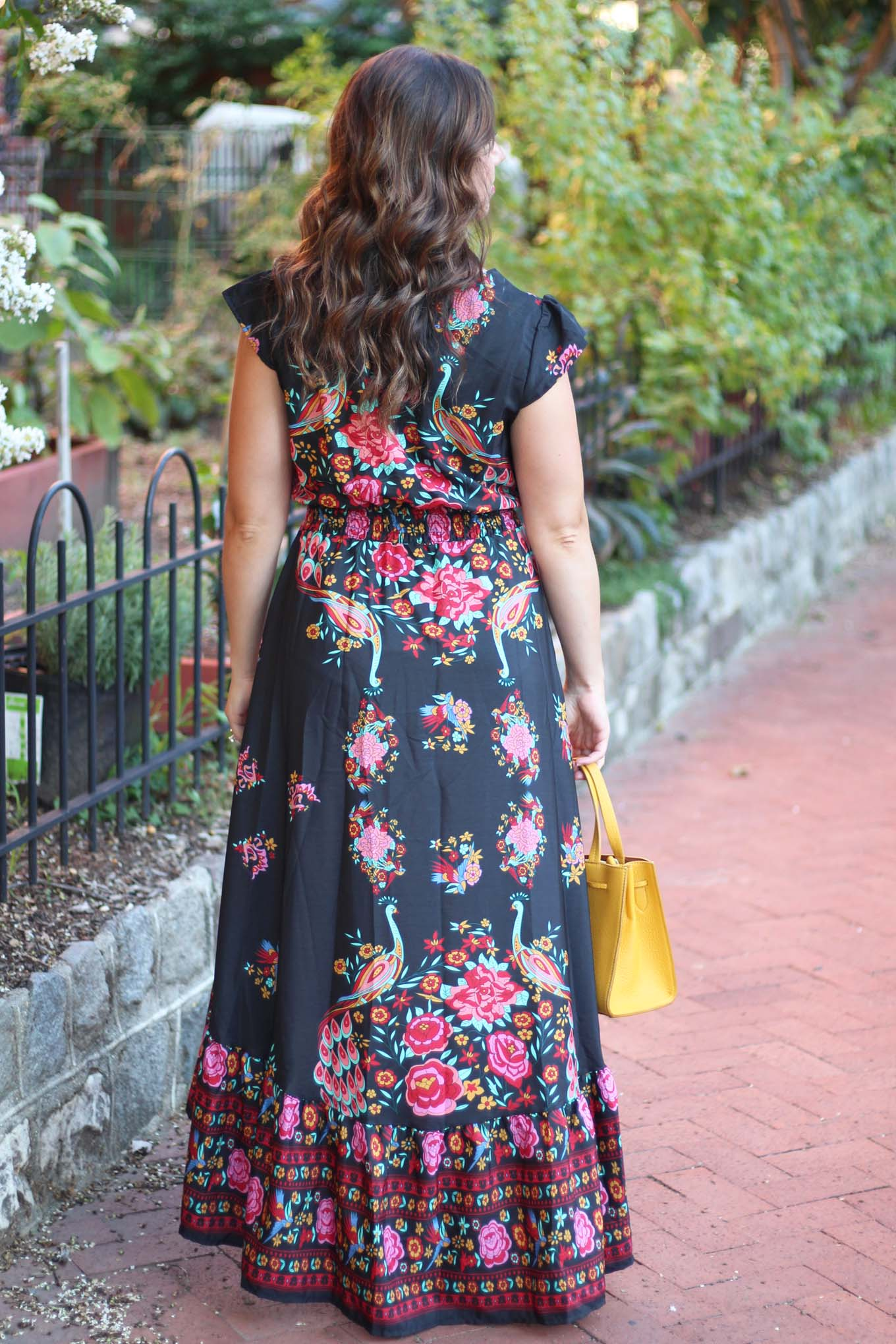 Lifestyle blogger Roxanne of Glass of Glam wearing a navy blue floral high low dress, Kate Spade bag, and Baublebar Earrings