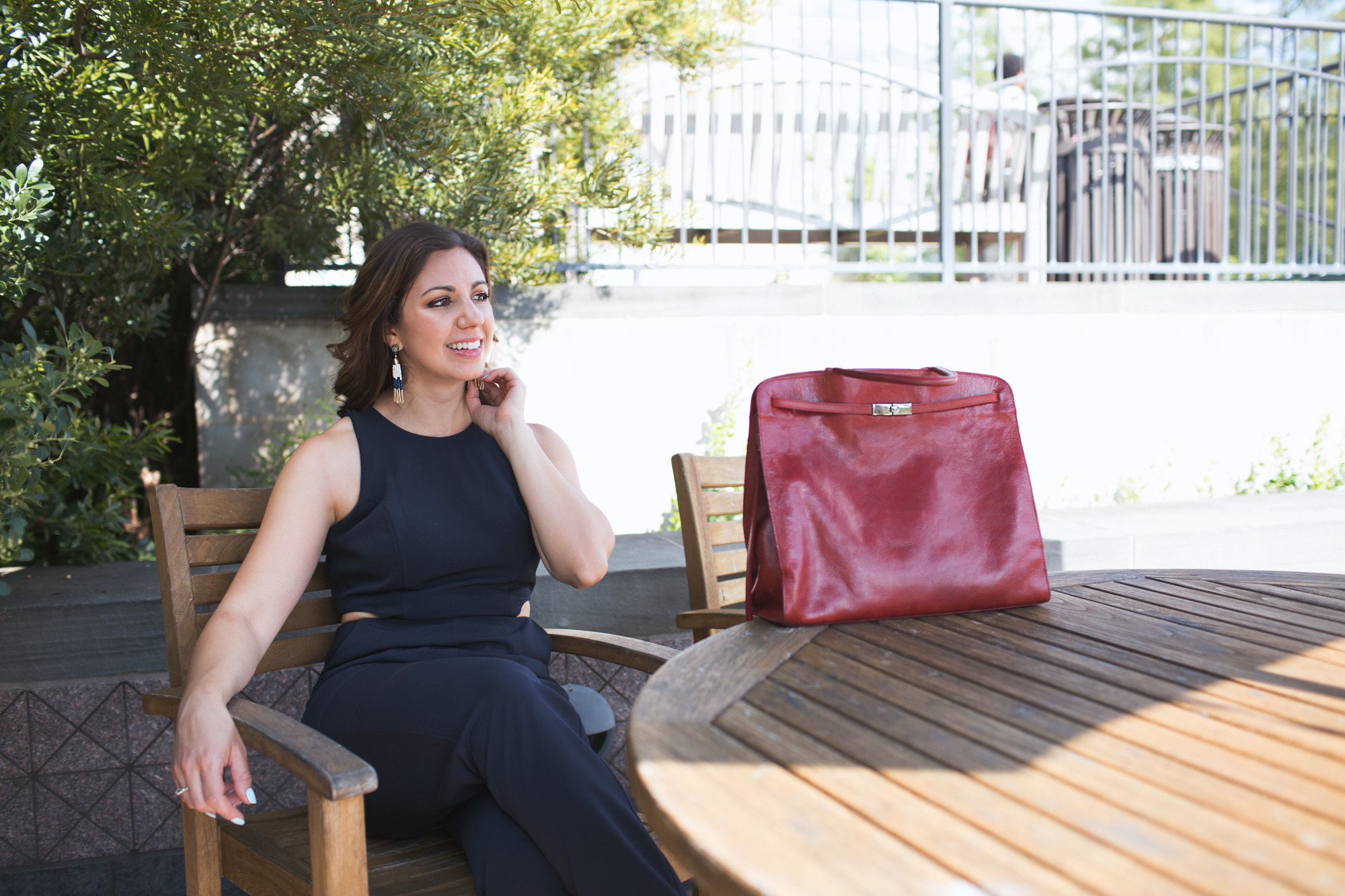 Lifestyle blogger Roxanne of Glass of Glam' styling a navy jumpsuit and vintage Furla bag from Current Boutique