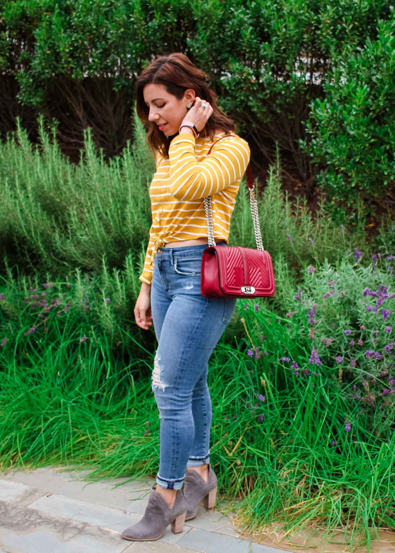 Lifestyle blogger Roxanne of Glass of Glam wearing a striped Shein crop top, A Gold E denim, and Vince Camuto Booties