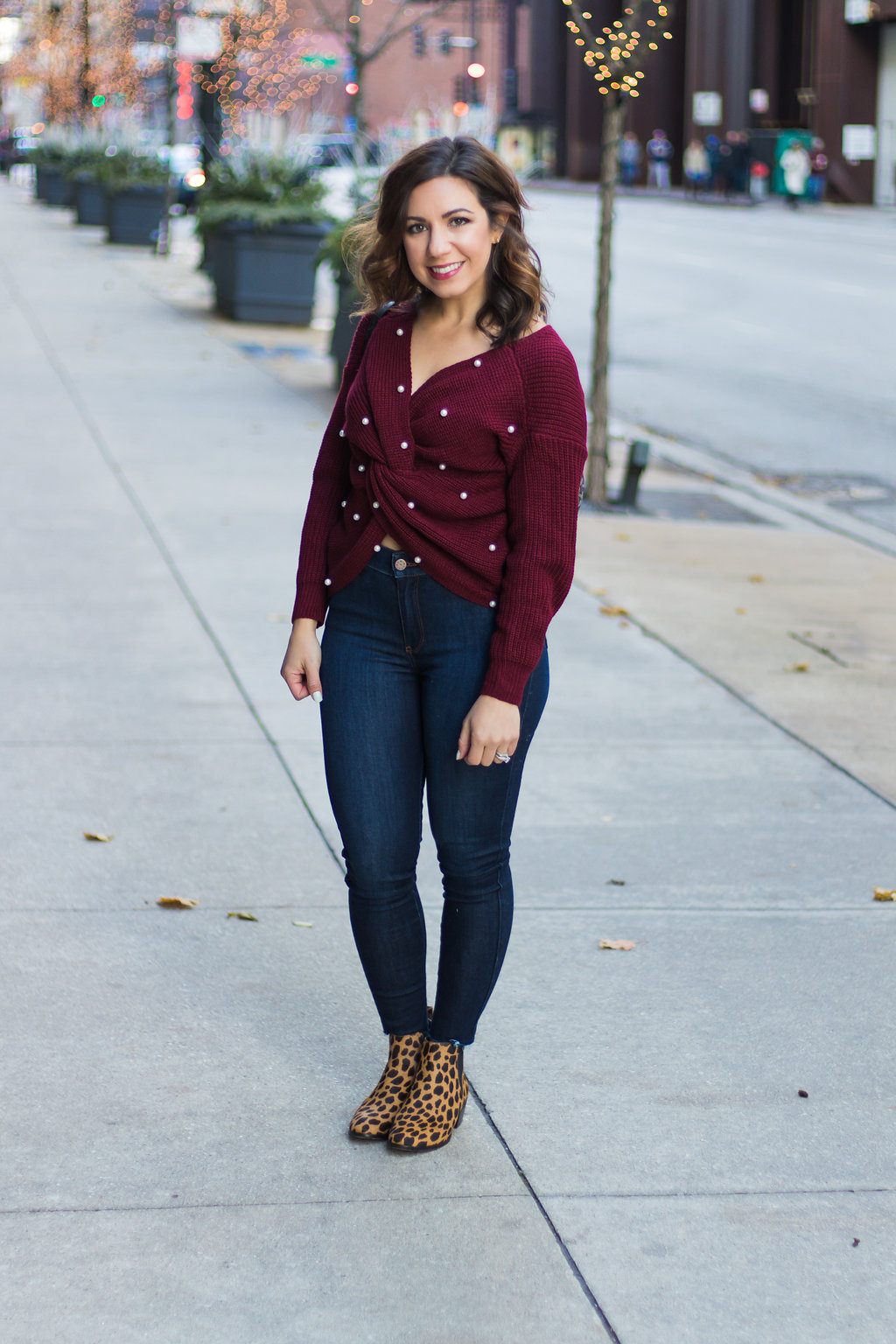 Lifestyle blogger Roxanne of Glass of Glam wearing a pearl burgundy sweater, green military jacket, Mott + Bow denim, and leopard booties