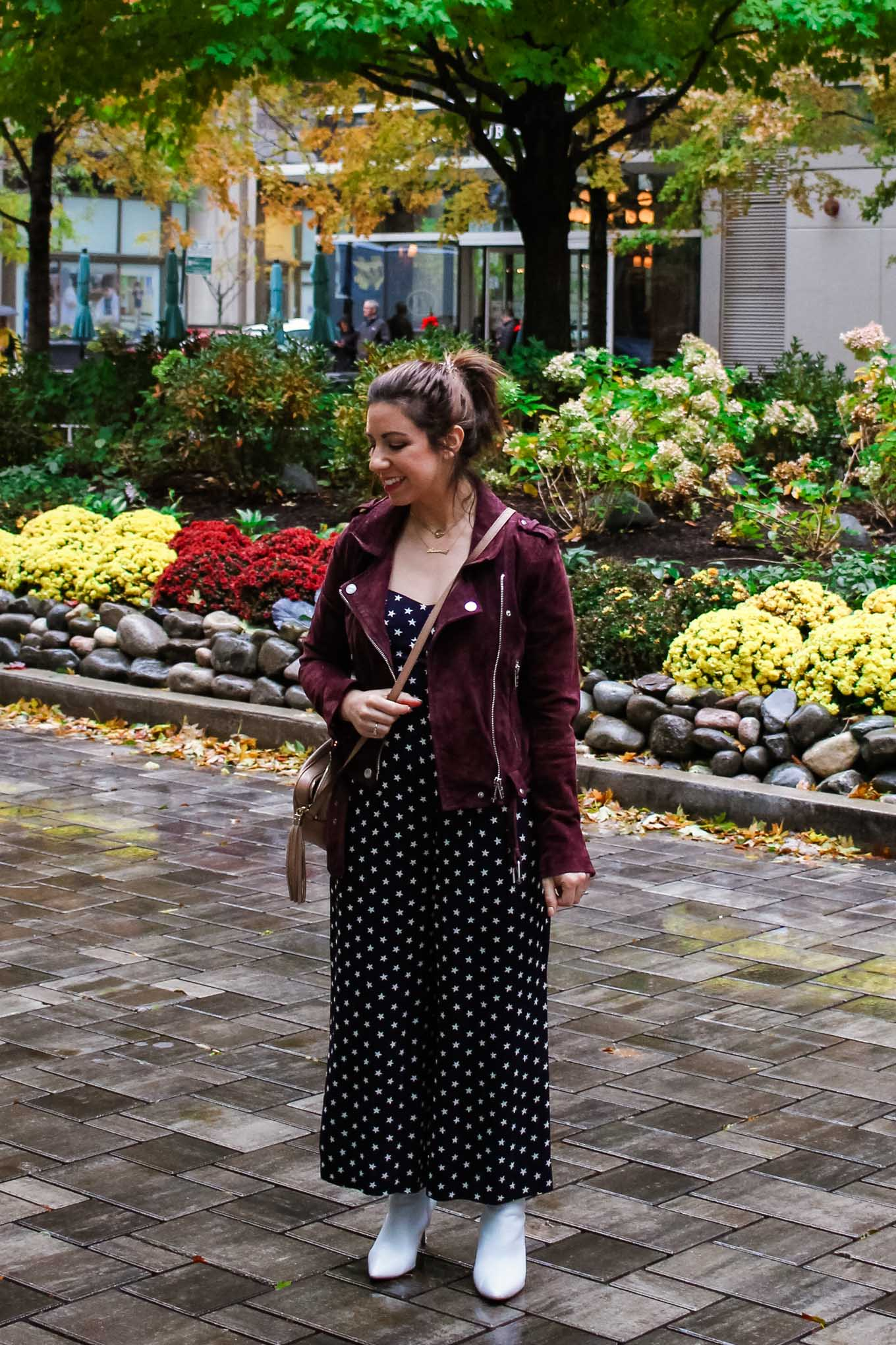 Lifestyle blogger Roxanne of Glass of Glam wearing a J.Crew star print jumpsuit, BlankNYC jacket, Halogen white booties, and a Gucci soho disco bag