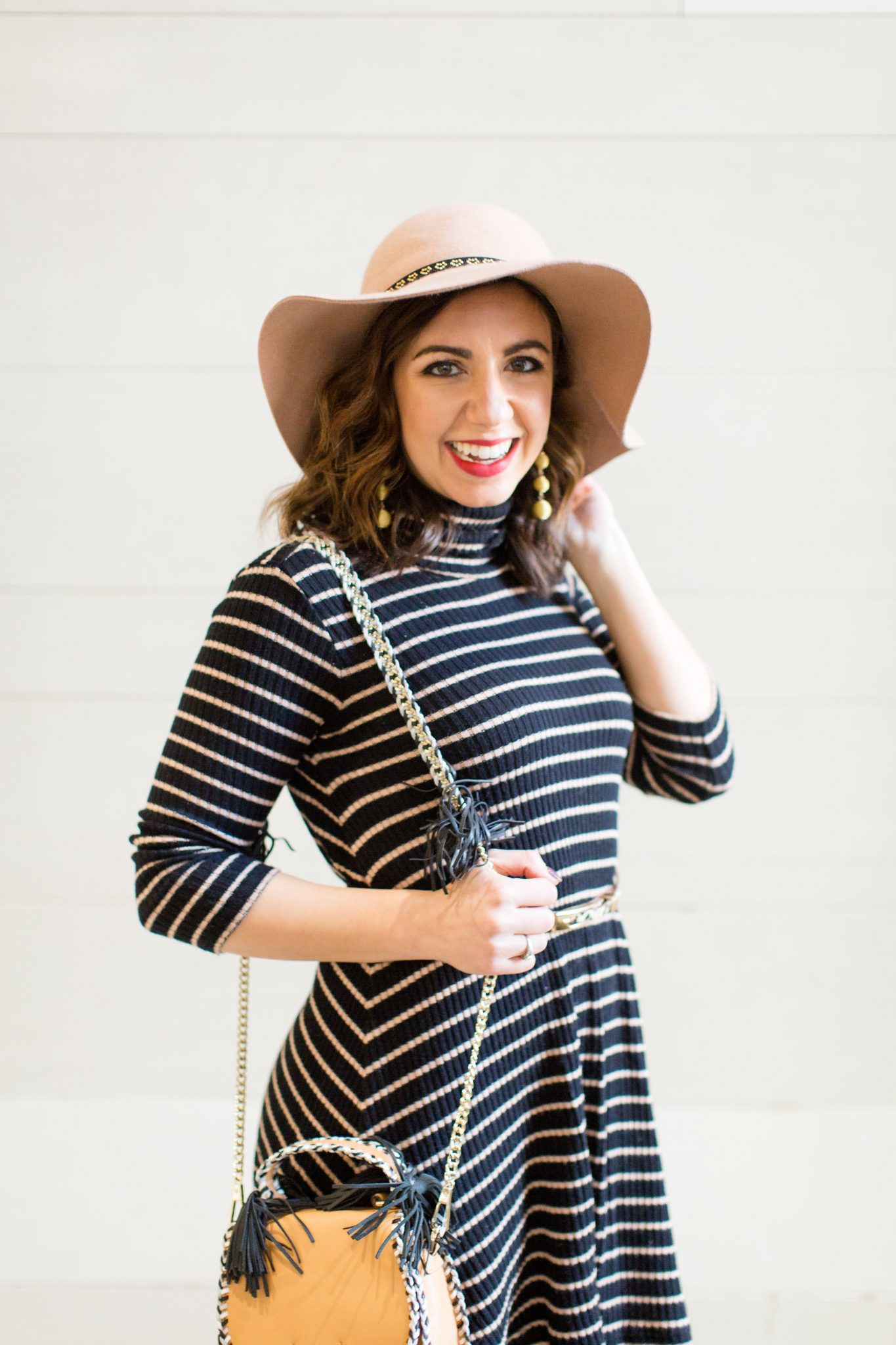 Lifestyle blogger Roxanne of Glass of Glam wearing a striped dress, Rebecca Minkoff bag, ted slouch booties, and fishnet tights