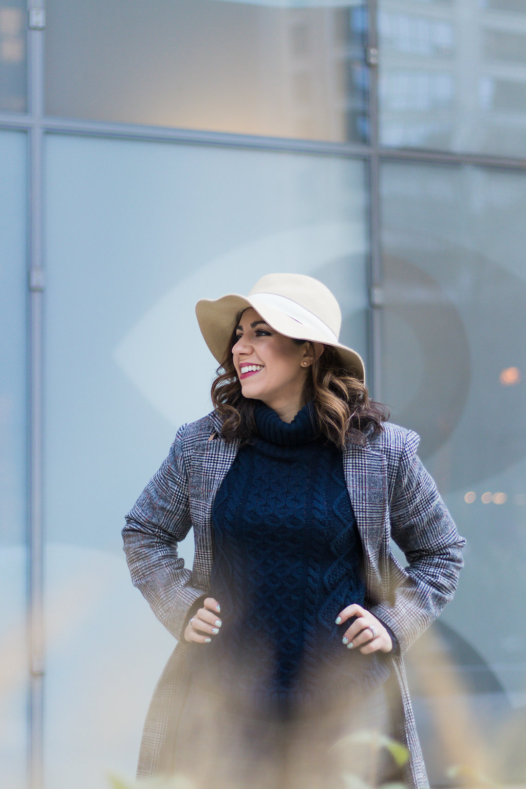Lifestyle blogger Roxanne of Glass of Glam wearing plaid pants, a plaid coat, felt fedora, and a cable knit sweater
