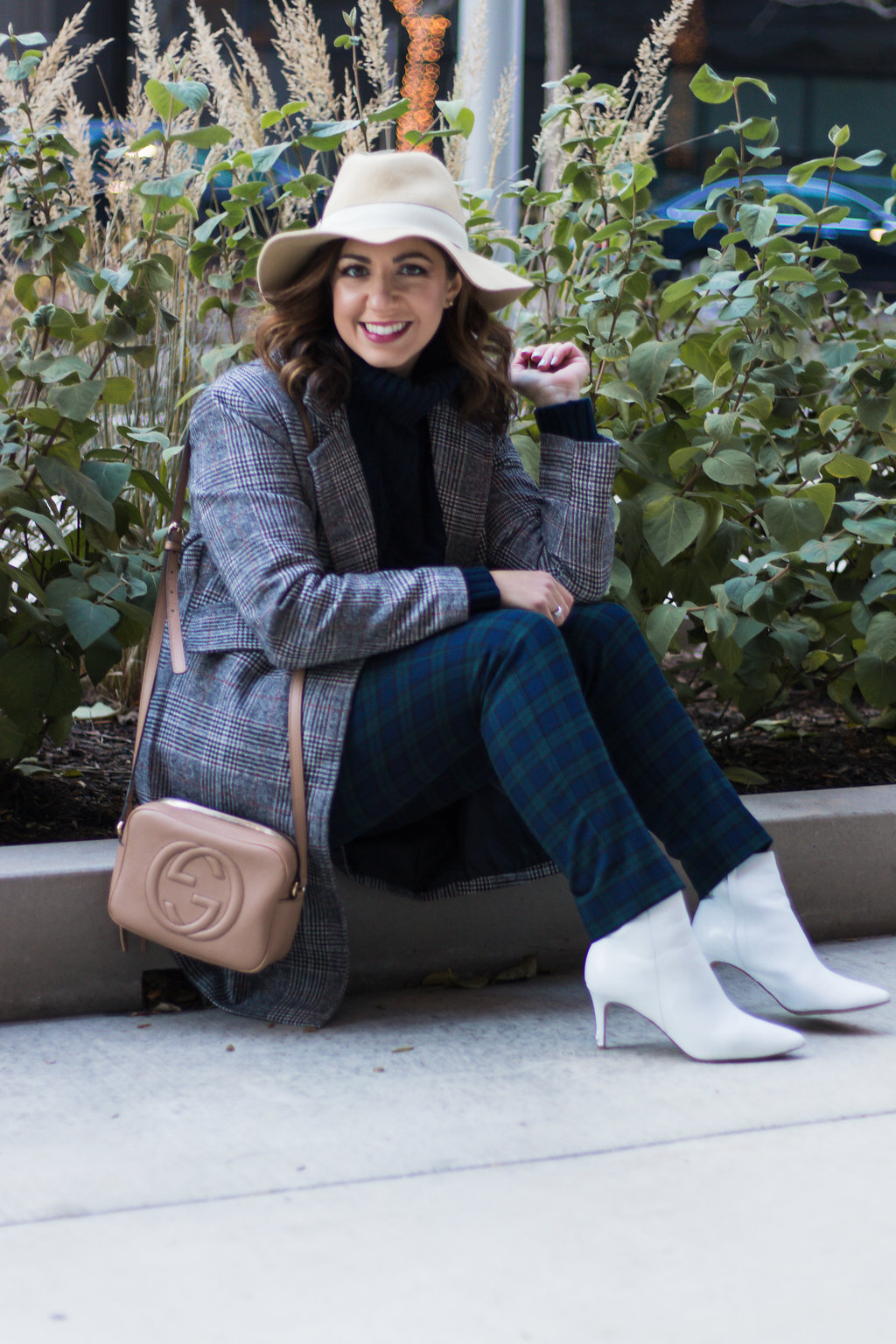 Lifestyle blogger Roxanne of Glass of Glam wearing plaid pants, a plaid coat, felt fedora, white booties, and a cable knit sweater
