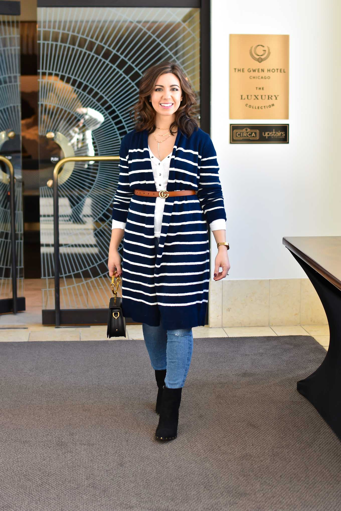 Lifestyle blogger Roxanne of Glass of Glam wearing an Old Navy cardigan, Urban Outfitters Henley, Agolde denim, Justfab booties, a Gucci belt replica (Gucci Dupe), and a Chloe Nile Dupe - Designer Dupes, White & Blue by popular DC fashion blogger Glass of Glam