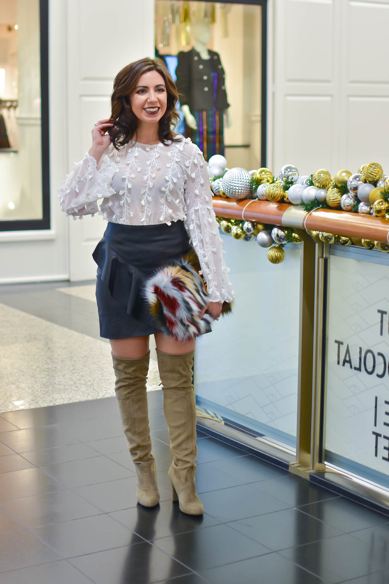 Lifestyle blogger Roxanne of Glass of Glam wearing a faux leather skirt, Shein embroidered blouse, faux fur clutch, and Steve Madden boots - Golden Birthday Wisdom by popular Chicago fashion blogger Glass of Glam