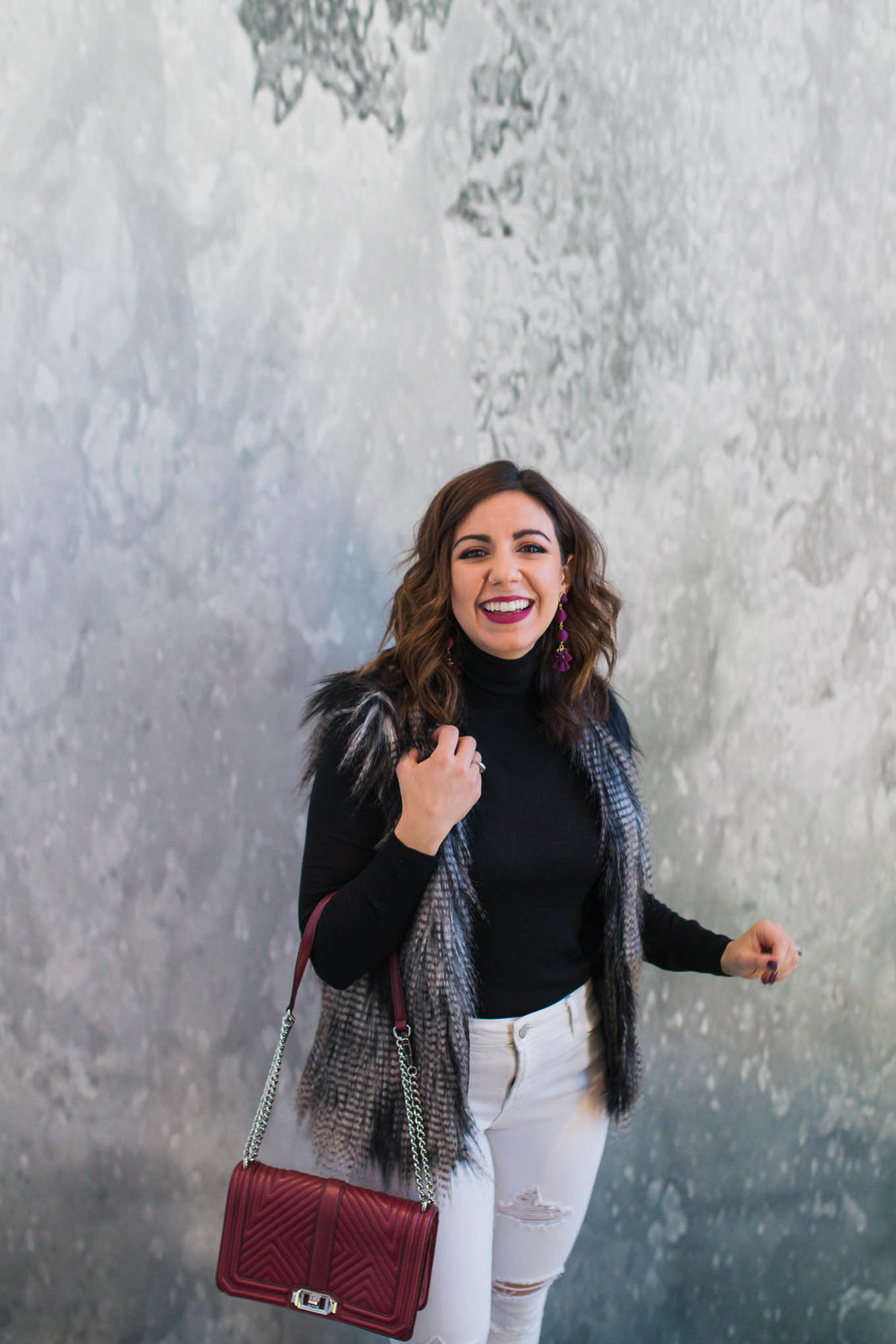 Lifestyle blogger Roxanne of Glass of Glam wearing a faux fur vest, J.Crew turtleneck, Old Navy white denim, and Baublebar earrings