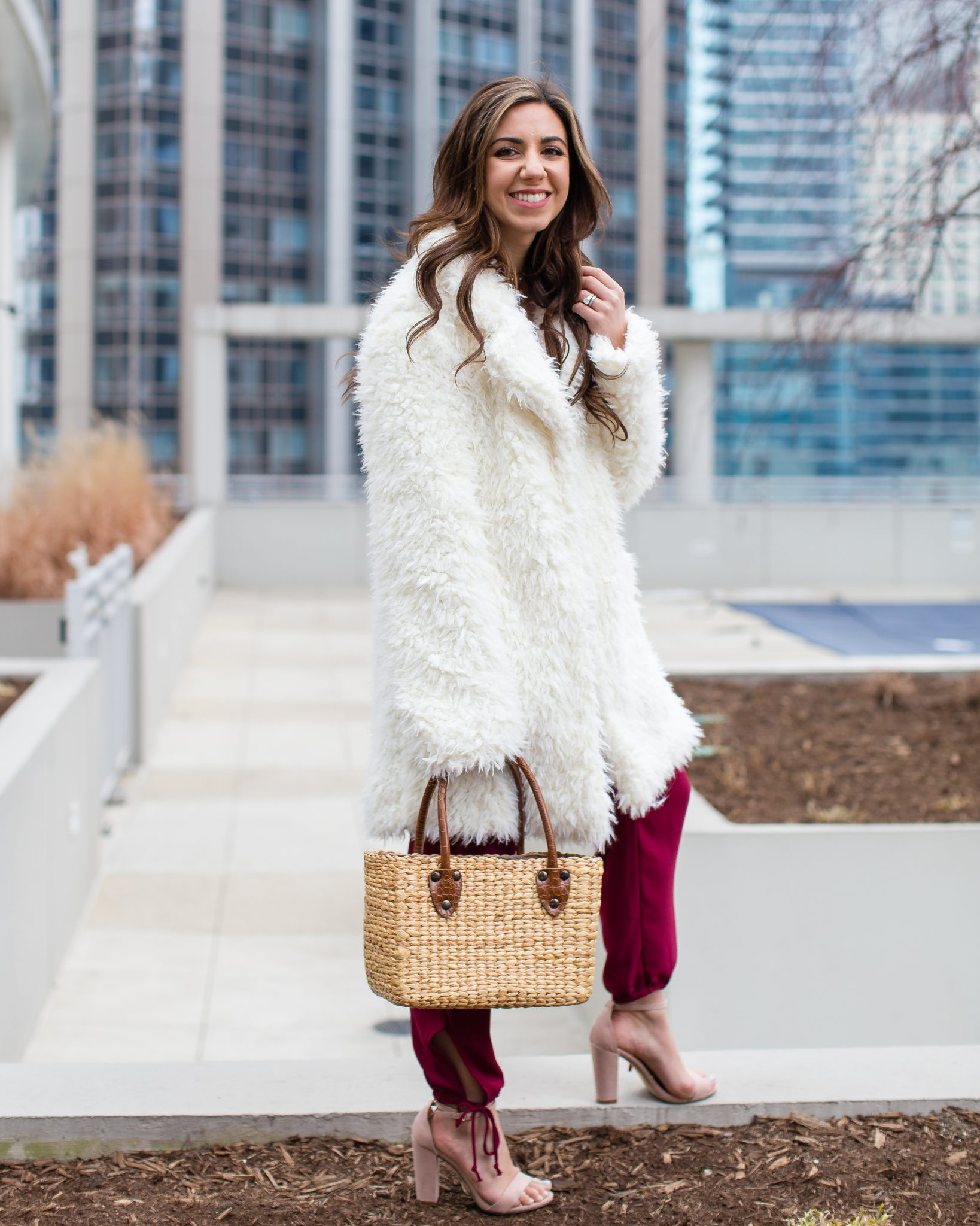 Lifestyle blogger Roxanne of Glass of Glam wearing a shaggy coat, burgundy pants, Sea and Grass straw tote, and a le tote necklace - How I Shoot Blog Photos by popular Chicago style blogger Glass of Glam
