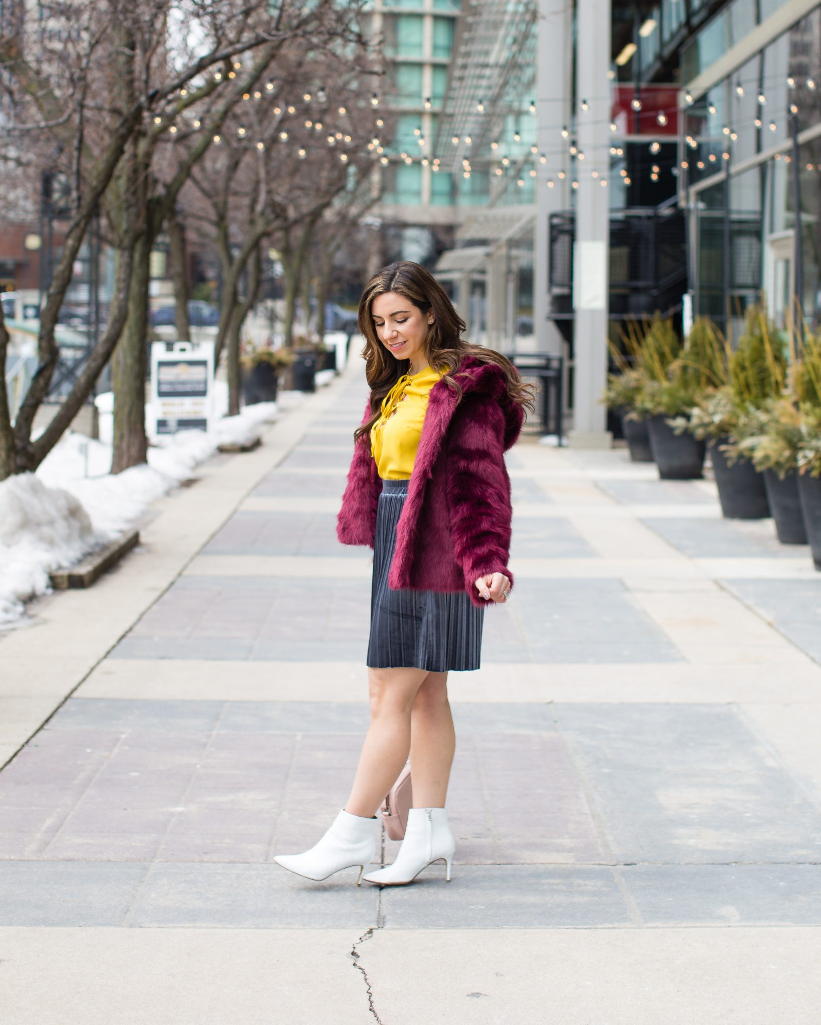 Lifestyle blogger Roxanne of Glass of Glam wearing a missguided faux fur coat, Shein mustard top, Asos velvet skirt, and white booties - A primary colors outfit by popular Chicago fashion blogger Glass of Glam