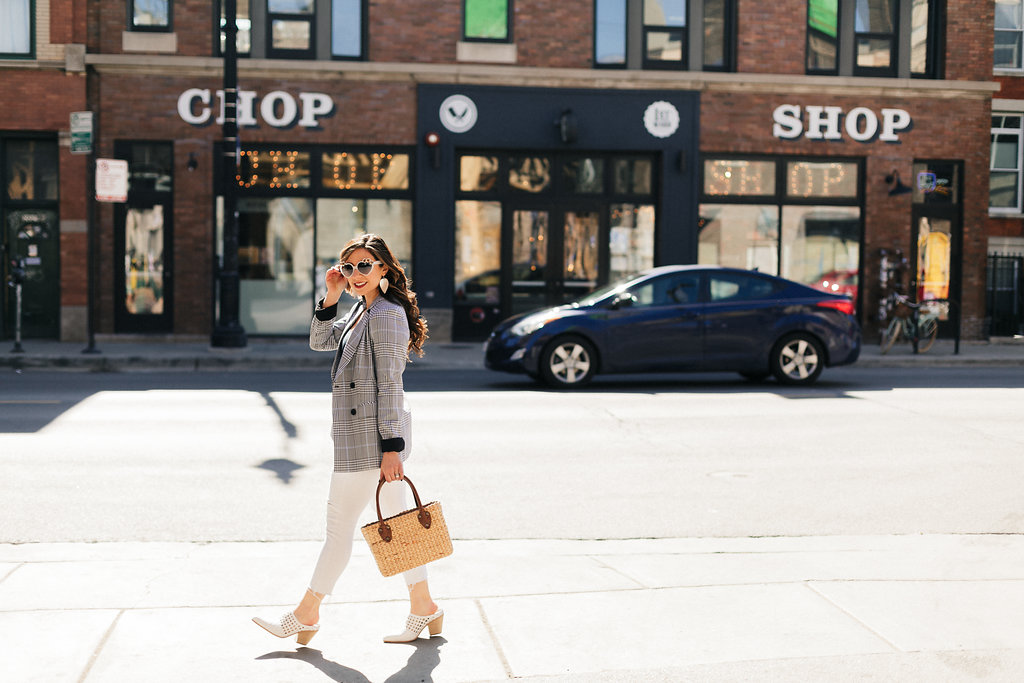 Lifestyle blogger Roxanne of Glass of Glam wearing a checked blazer, white denim, Jeffrey Campbell white mules, heart sunnies, and a straw bag. - Checked Blazer styled by popular Chicago fashion blogger Glass of Glam