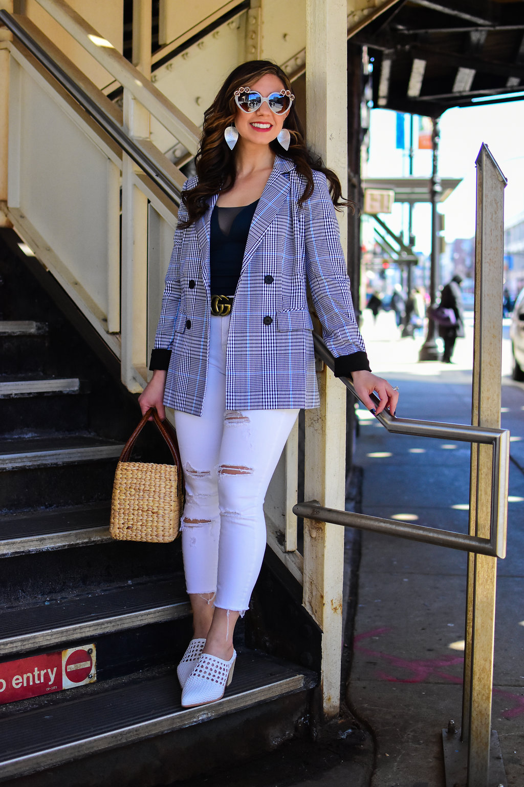 Lifestyle blogger Roxanne of Glass of Glam wearing a checked blazer, white denim, Jeffrey Campbell white mules, heart sunnies, and a straw bag.