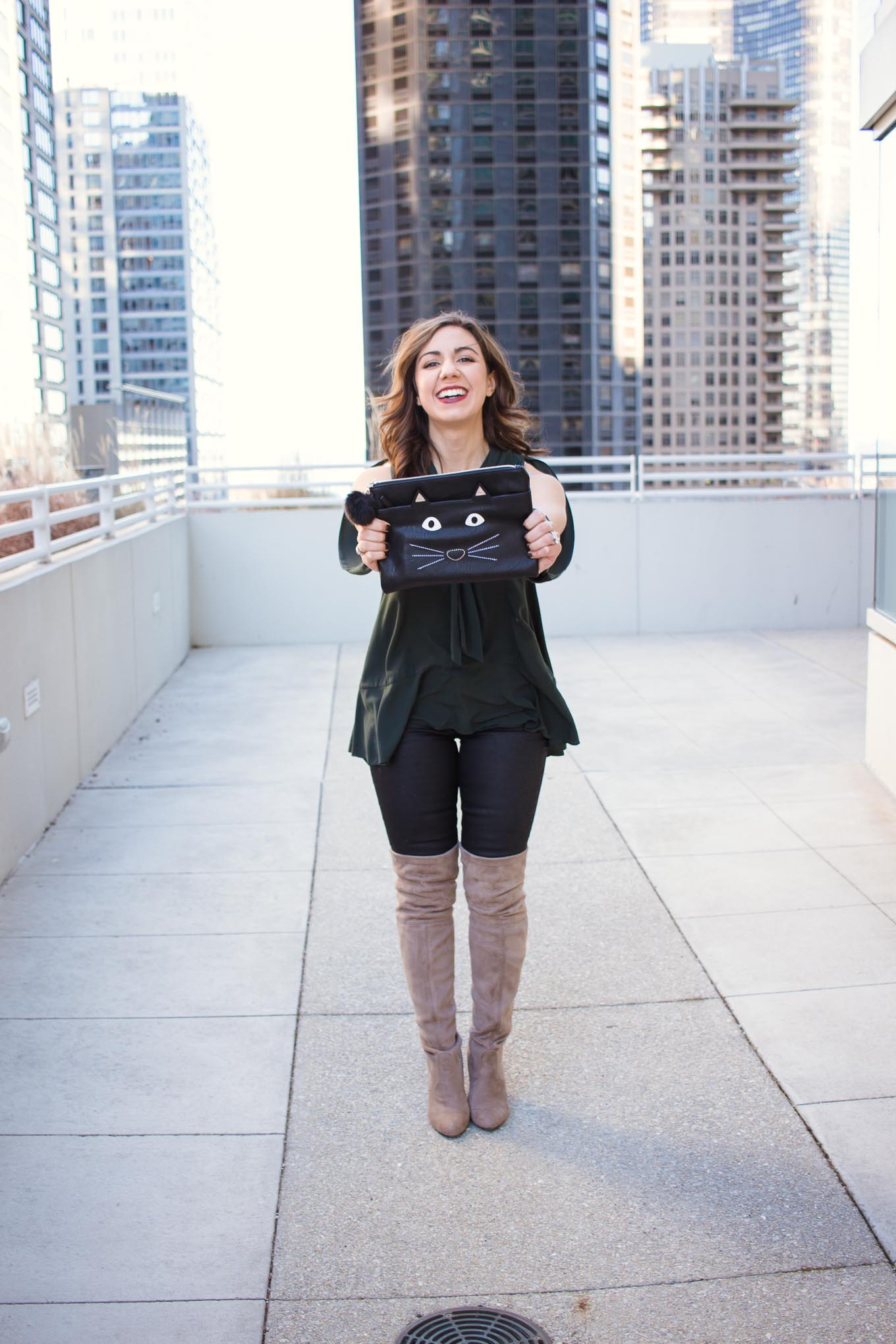 Lifestyle blogger Roxanne of Glass of Glam wearing a Le Tote green top, coated denim, cat clutch, and steve madden boots