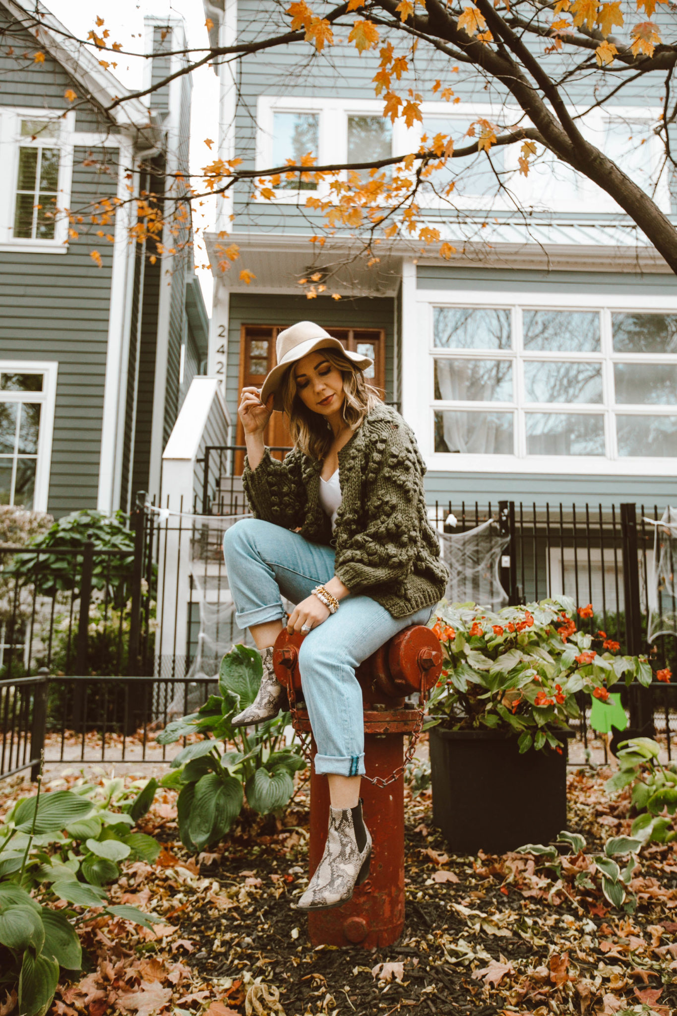 Five Fall Boot Trends by popular Chicago fashion blog, Glass of Glam: image of a woman outside wearing snake skin print boots.