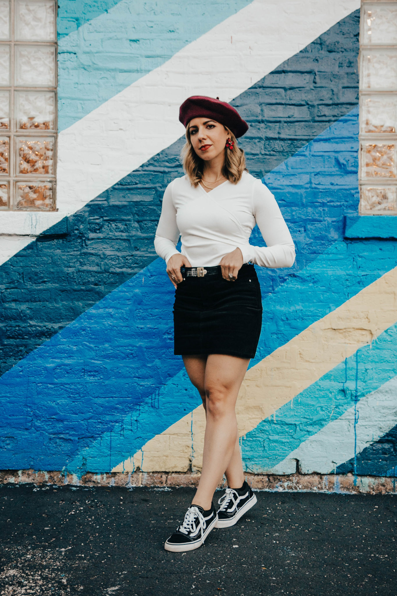 Stay truly informed featured by top US lifestyle blog, Glass of Glam: image of a woman standing in front of a rainbow wall wearing an H&M corduroy skirt, a SheIn bodysuit, Vans Old Skool and a red beret