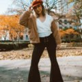| Black Bell Bottoms and 70s style featured by top Chicago fashion blog, Glass of Glam: image of a woman wearing Show Me your MuMu black bell bottoms, Show me your mums white top, SheIn faux fur teddy jacket, Steve Madden Lulla Sandals and a Brixton fiddle cap
