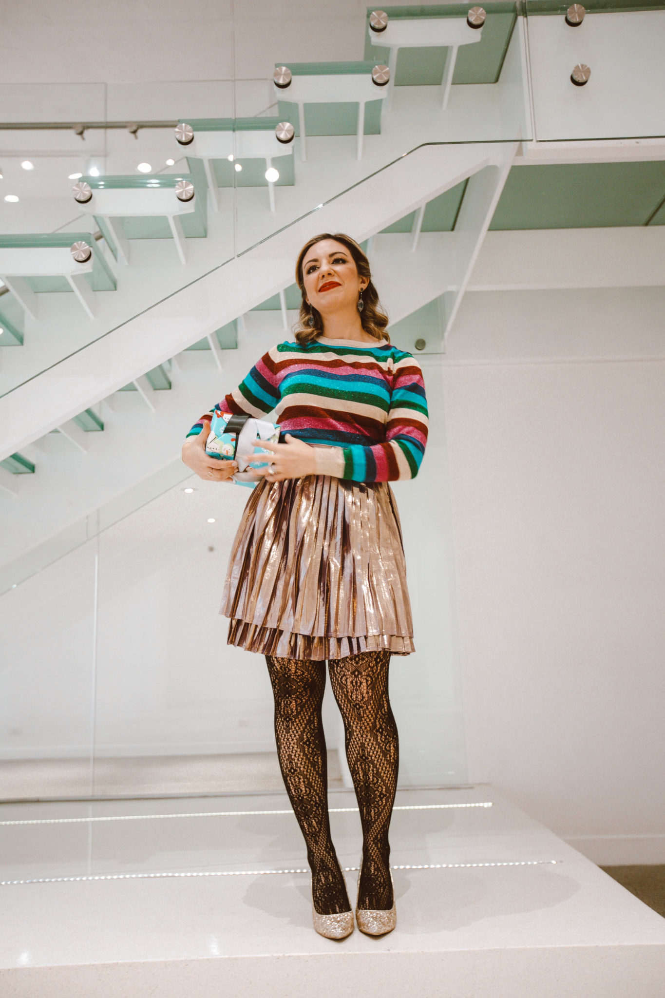Last Minute Gift Ideas Under $50 featured by top Chicago life and style blog, Glass if Glam: image of a woman holding a wrapped present and wearing a metallic skirt, floral tights and a striped top