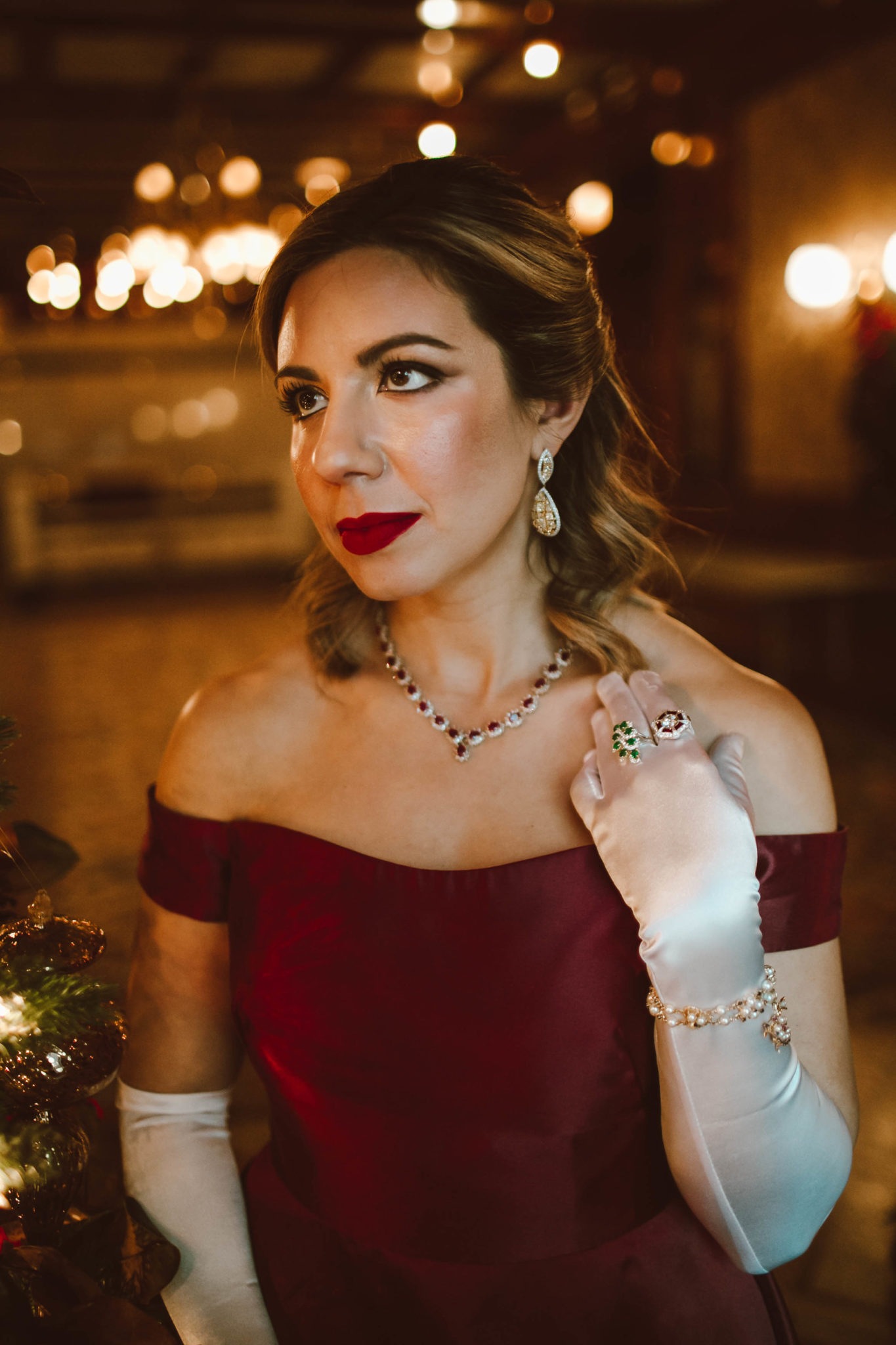 Glamorous holiday look featured by top Chicago fashion blog, Glass of Glam: image of a woman wearing a Monique Lhuillier gown, a Gigi New York clutch, glitter stiletto pumps, Amazon satin gloves