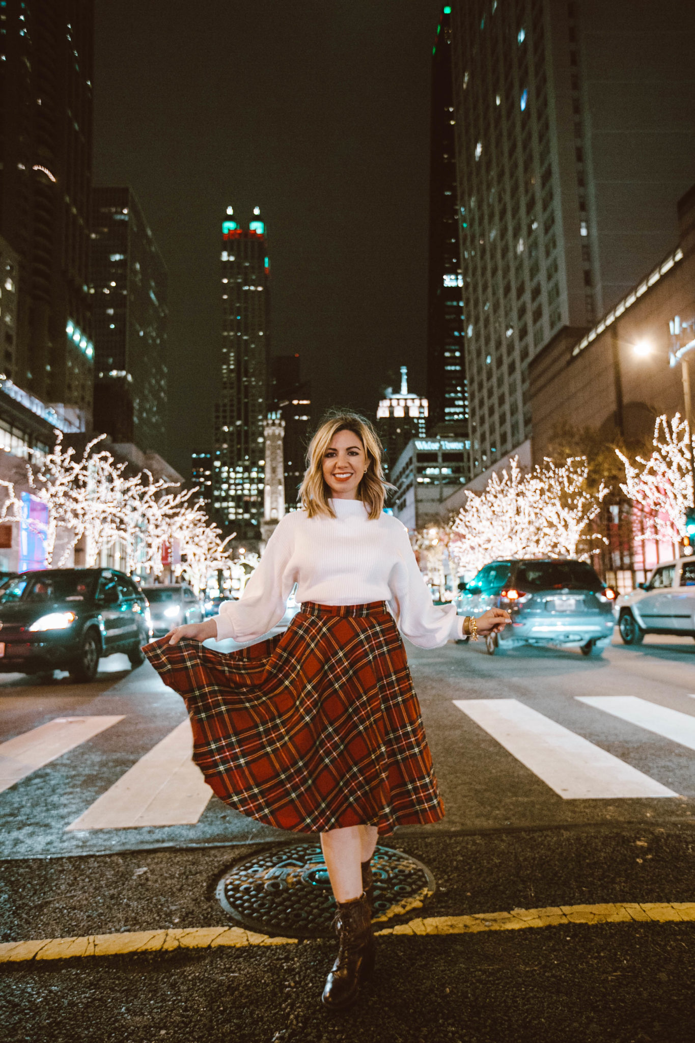 Best Chicago winter activities featured by top Chicago blog, Glass of Glam: picture of a woman in Chicago wearing a Happy Goat Lucky long puffer coat, Modcloth plaid skirt, Line & Dot sweater and Patricia Nash booties
