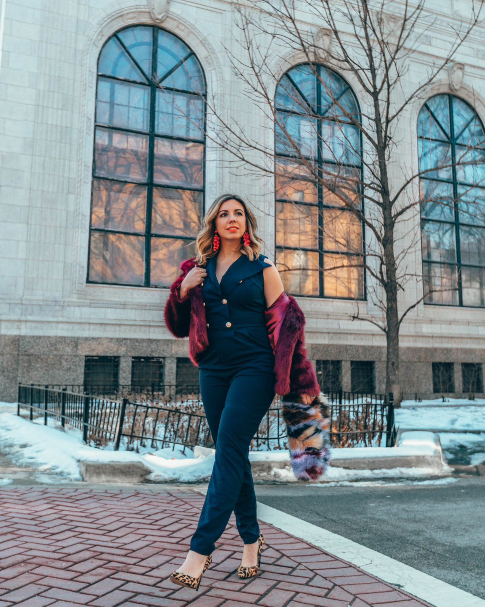 Blue jumpsuit styled for Spring by top US fashion blog, Glass of Glam: image of a woman wearing a SHEIN blue jumpsuit, SHEIN faux fur clutch bag, TOPSHOP faux fur coat, Sam Edelman leopard pumps, Baublebar earrings.