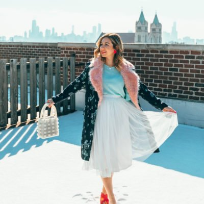 White tulle skirt styled by top US fashion blog, Glass of Glam: image of a woman wearing an ASOS white tulle skirt, SheIn Aqua top, Amazon pink sandals, Rent the Runway floral coat, BaubleBar heart pendant necklace, Baublebar heat earrings and an Amazon beaded handbag