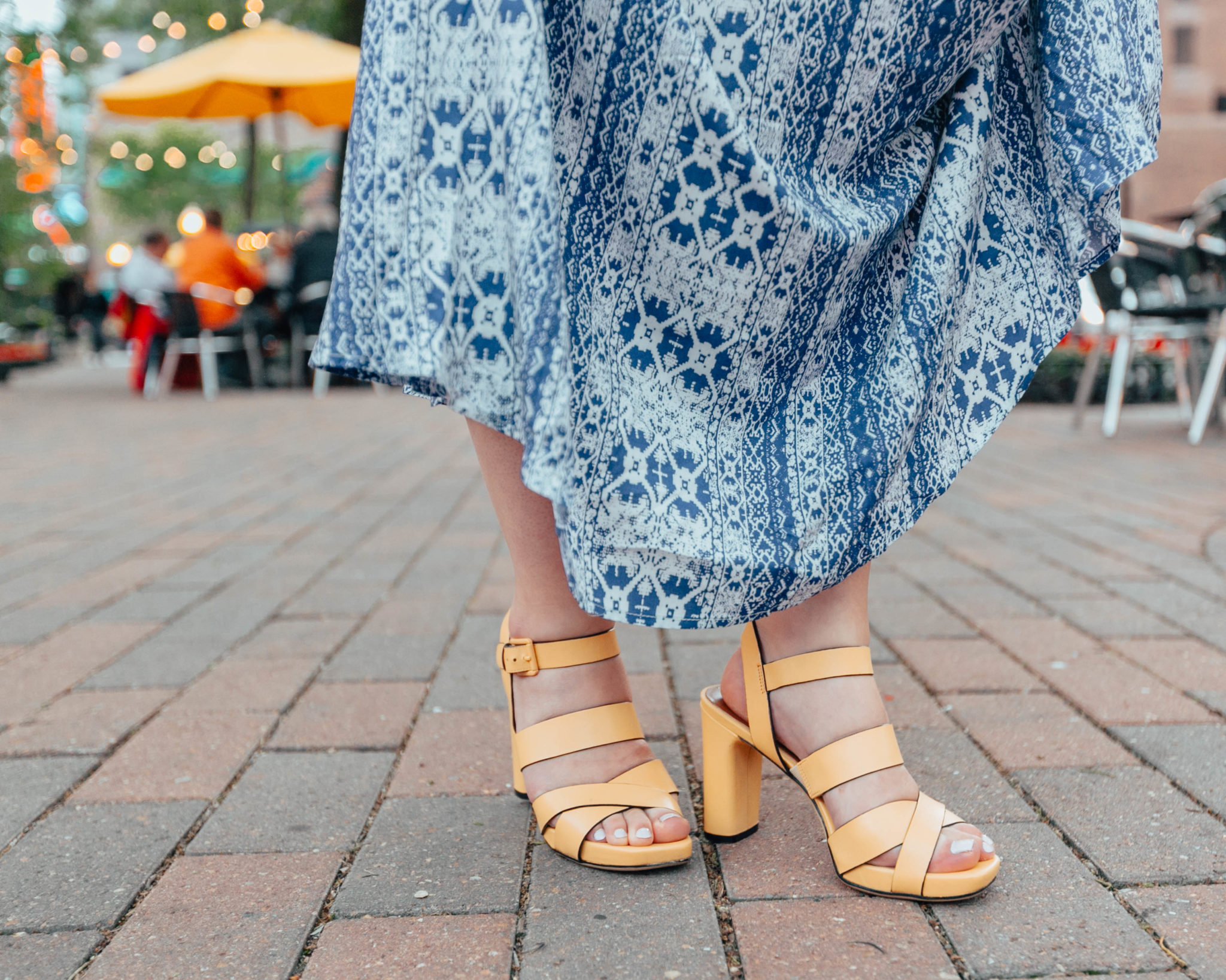 The Best Summer Sandals Styles featured by top US fashion blog, Glass of Glam: image of a woman wearing yellow Naturalizer sandals.