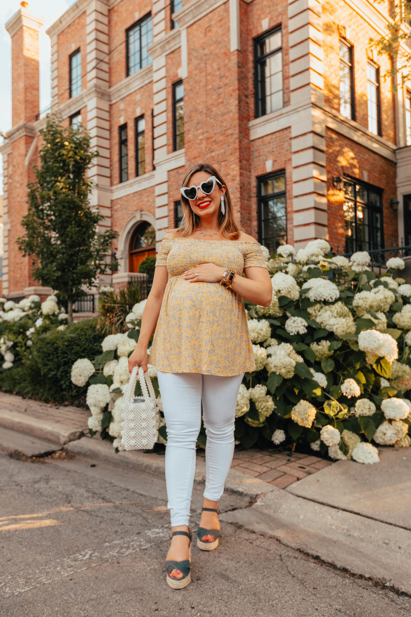 Summer maternity outfit featured by top US fashion log, Glass of Glam: image of a pregnant woman wearing an Ingrid & Isabel off the shoulder flower top, Old Nave Maternity white denim, Castaner low wedges, Miuco pearl tote bag, Kendra Scott necklace, SUGARFIX beaded earrings, and MINCL heart sunglasses.