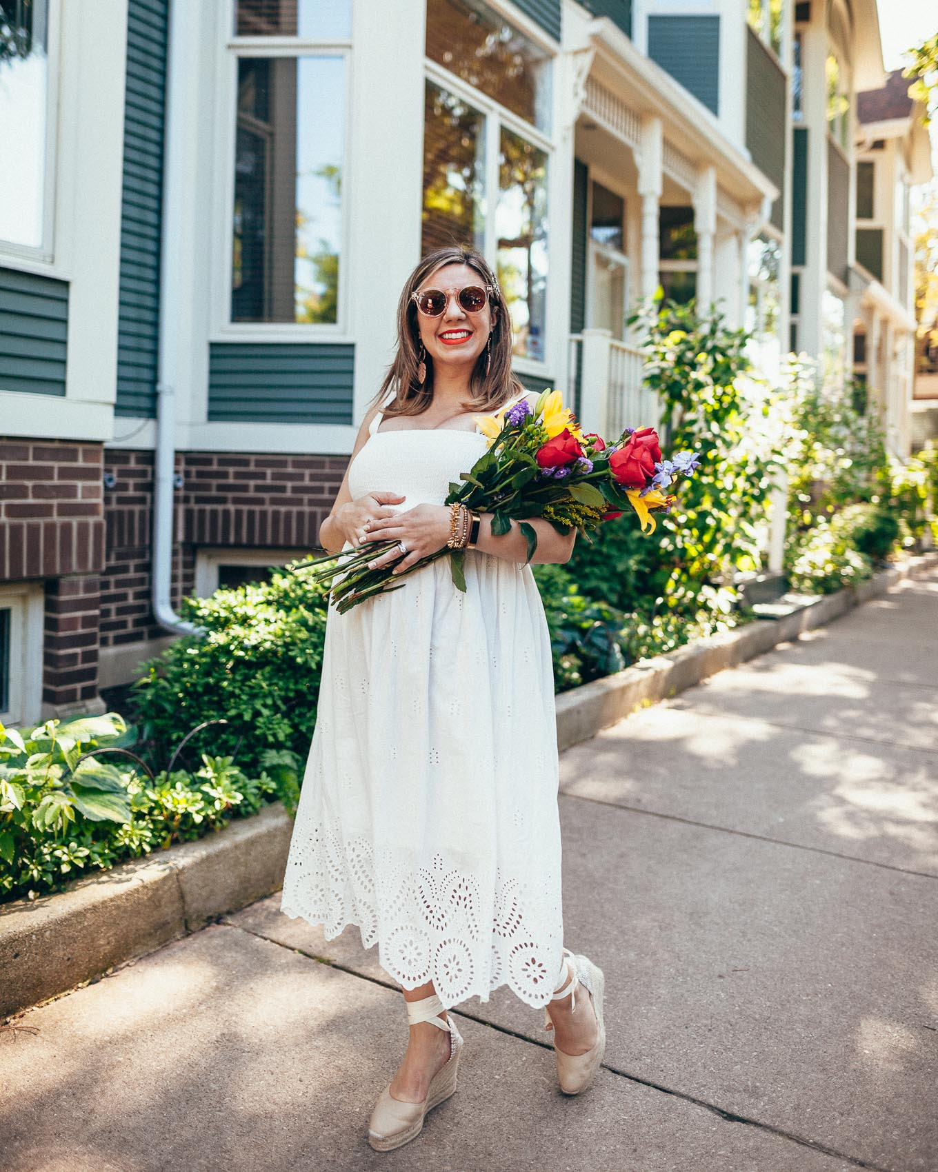 Little White Summer Dress & The Return of The Magnificent 8 by popular fashion blog, Glass of Glam: image of a woman holding a bouquet of flowers and walking down a street wearing an Embroidered Scallop Hem Maternity Dress, Shopbop Castaner Espadrilles, WODISON Women's Retro Mirrored Sunglasses, Sephora lipstick, Nordstrom Ettika Palm Leaf Drop Earrings, Bracelet Strap Replacement Wristband Magnetic Lock for Alta, Stella and Dot Renegade Cluster Bracelet, and Stella and Dot Nicholette Stretch Bracelet.