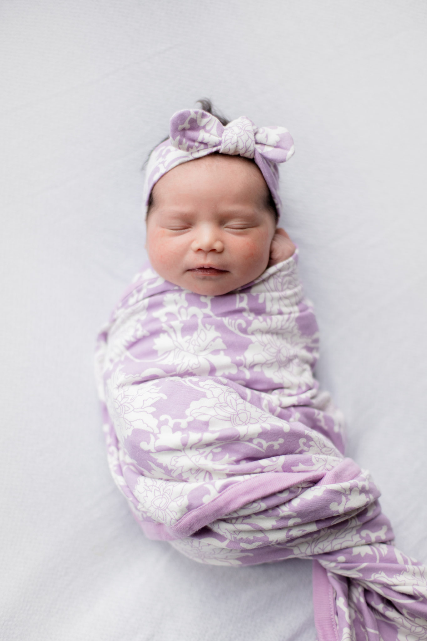 Baby Girl Birth Story: Welcome Sidney Eileen! by popular life and style blog, Glass of Glam: image of a baby girl swaddled in a purple and white floral print blanket.