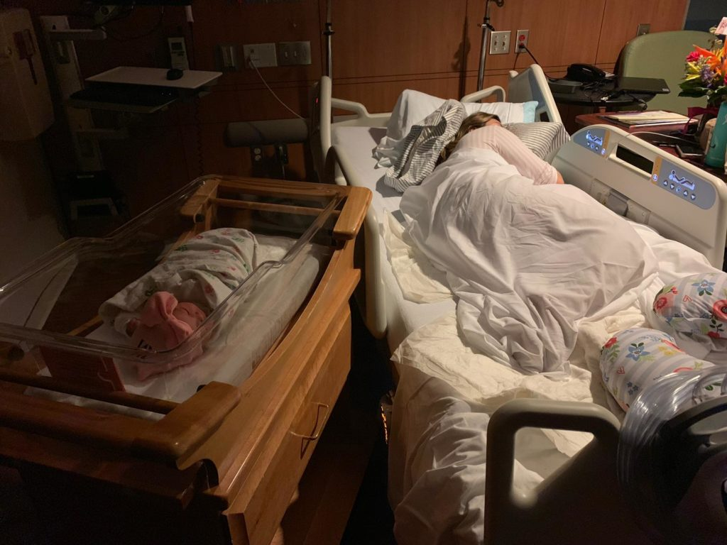 Baby Girl Birth Story: Welcome Sidney Eileen! by popular life and style blog, Glass of Glam: image of a woman sleeping in a hospital bed with newborn baby girl laying in a baby bed in postpartum recovery room at the hospital.