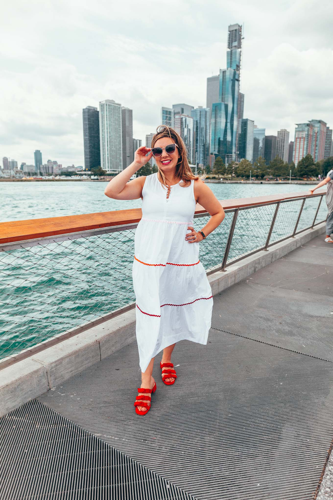 Transitioning After Pregnancy - What Is Post Pregnancy Like? by popular Chicago life and style blog, Glass of Glam: image of a woman standing outside with the Chicago skyline behind her and wearing a Madewell Rickrack Cattail Tiered Dress and Sole Society Ezah Bow Slide Sandal.