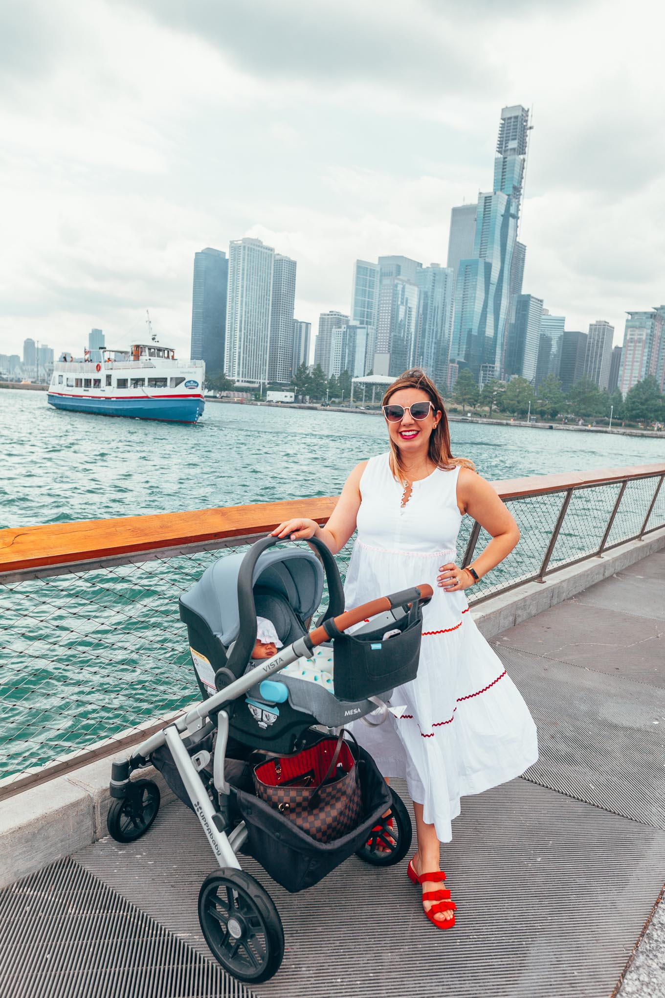 Transitioning After Pregnancy - What Is Post Pregnancy Like? by popular Chicago life and style blog, Glass of Glam: image of a woman standing outside by a river with her baby in a baby stroller and wearing a Madewell Rickrack Cattail Tiered Dress and Sole Society Ezah Bow Slide Sandal.
