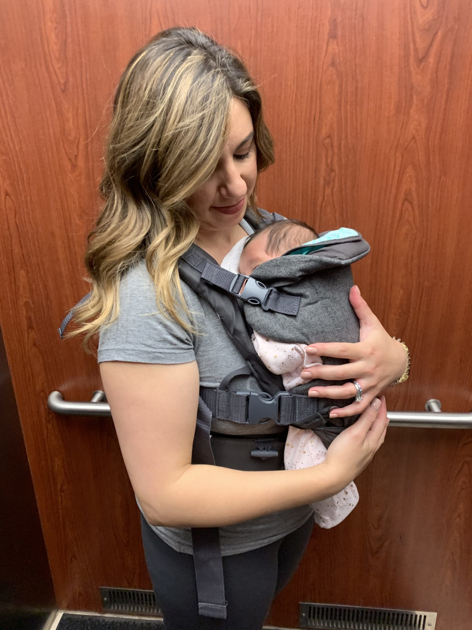Best of Baby Month: Huge Savings On Baby Gear! by popular Chicago life and style blog, Glass of Glam: image of a woman holding her newborn baby in a baby carrier.